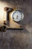 Pocket-watch and rusty keys on wooden texture background.