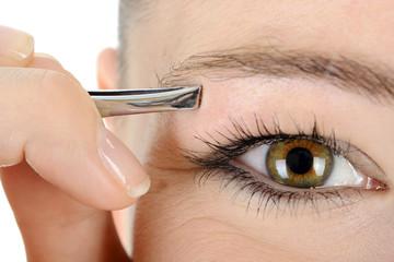 Frau zupft sich die Augenbrauen