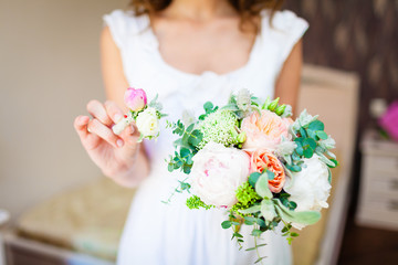 bride holding a wedding bouquet and a buttonhole