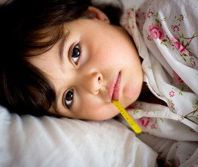 little girl with thermometer in bed
