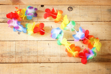 Necklace of bright colorful flowers lei on wood background