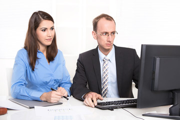 Two business people sitting at desk.