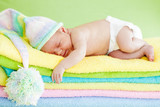 newborn baby girl sleeping on color towels