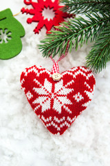 Knitted  heart on the snow with fir-tree branch