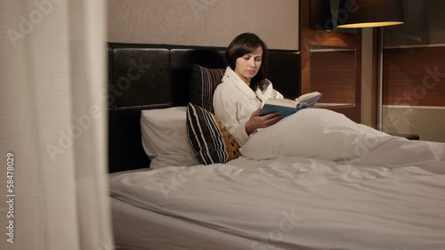 gorgeous brunette reading a book in bed in a high end hotel room