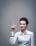 Business woman with finger pointing isolated against dark backgr