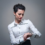 Business worried woman looking at the time on her wrist watch.