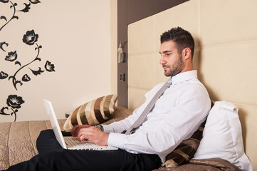 Young businessman working with computer in hotel room.