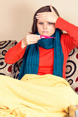 Young woman having flu and  checking a thermometer