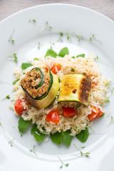 Tomaten-Reis auf Ruccola mit vegetarischen Zucchiniröllchen