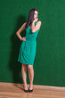brunette in green dress against wall