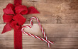 Candy canes and ribbon on wooden background