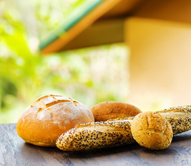 Fresh bread on black wooden table on rural landscape background
