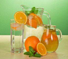 Jugs with drinks, glass and oranges