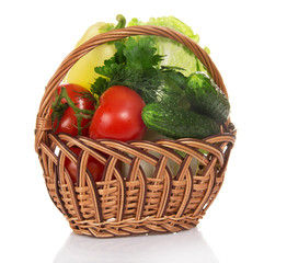 Cabbage, tomatoes, cucumbers, pepper in wicker basket