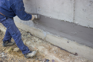 Construction worker with brush applied hydro insulation