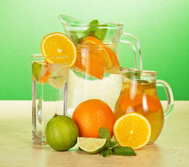 Jugs and glass with oranges juicy