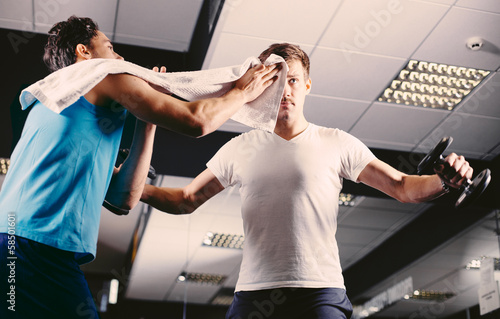 Young man wiping sweat off of friend's face in gym