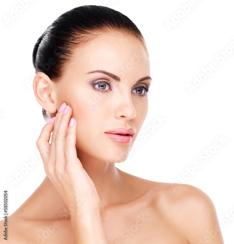 woman with fresh skin touching cheek by hand