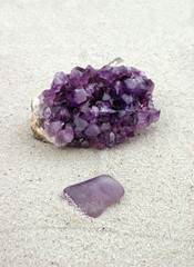 Rough and smooth purple crystals on sand