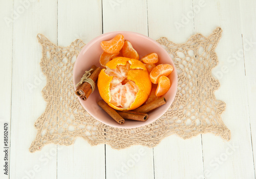 Tasty mandarines in color bowl on light background
