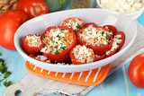 Stuffed tomatoes in bowl on wooden table close-up