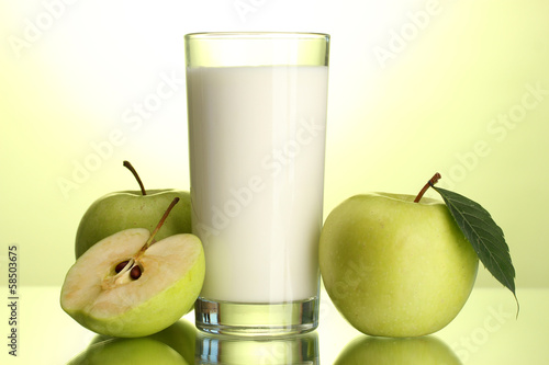 Glass of kefir and apples, on green background