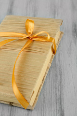 Book wrapped with color ribbon, on color wooden  background