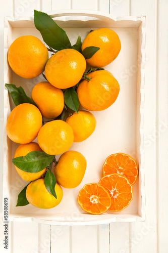 tangerines on light background in a wooden box.
