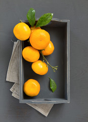 tangerines on a gray background in a wooden box.
