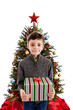 Child holding present in front of Christmas tree