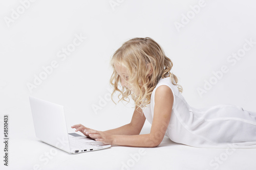 Beautiful blonde little girl with netbook, white background