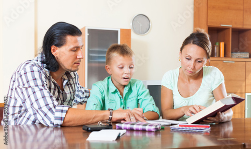 family of three doing homework in home