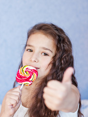 cute little girl eating a lollipop