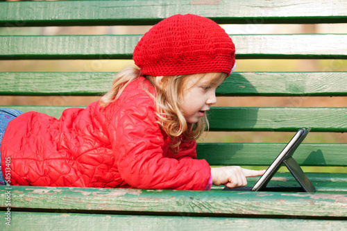 Happy smiling little girl working with tablet pc