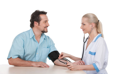 Attractive nurse measure the pressure of adult male patient