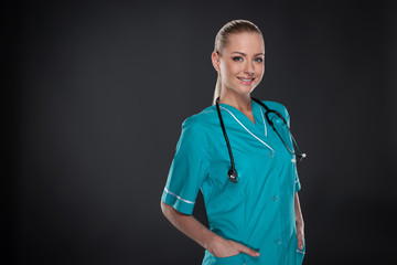 Young Blond nurse in green robe standing