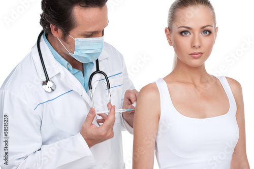 Doctor in mask doing vaccination to young attractive woman.