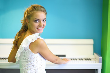A beautiful girl sitting at a white piano