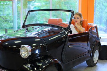 A pretty woman driving a retro black car