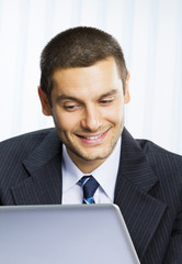 Smiling businessman working with laptop
