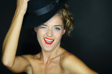 woman with bare shoulders and hat winks on dark