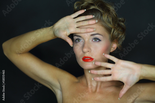 woman with bare shoulders and palms near face
