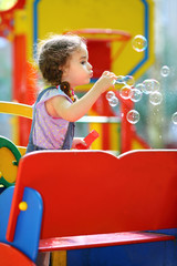Little girl blowing a lot of soap bubbles on the playground