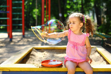 Little girl with tails sitting in a sandbox and blows bubbles