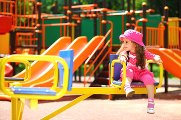 Smiling little girl in a pink hat whirls on the roundabout