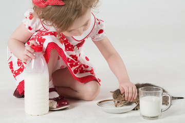 A little girl in a polka dot dress feeds a kitten by milk