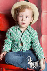 Little boy in a plaid shirt, jeans and hat sitting on chair