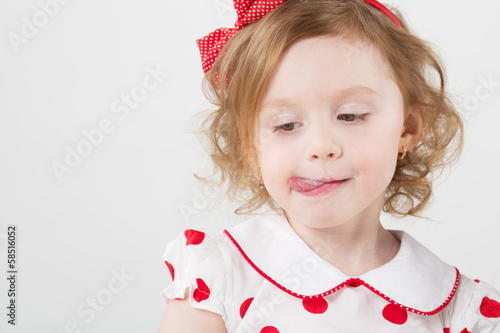 Little girl licking her lips covered with milk
