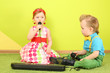 Boy and girl sitting on the floor in front of a toy piano